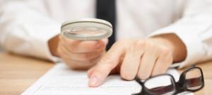 Focused businessman is reading through magnifying glass documen