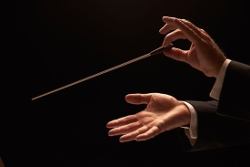 10423832 - conductor conducting an orchestra isolated on black background