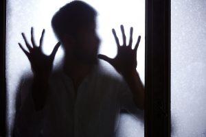 man-behind-window-P5EXRLF-300x200
